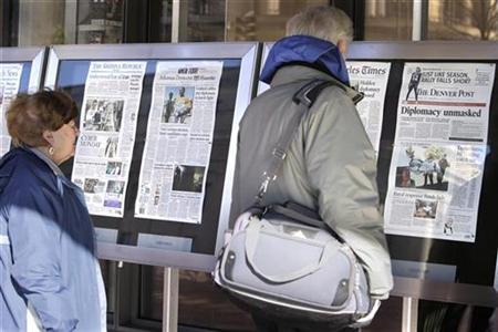 People read Monday's U.S. newspapers front pages outside the Newseum in Washington November 29, 2010. REUTERS/Yuri Gripas