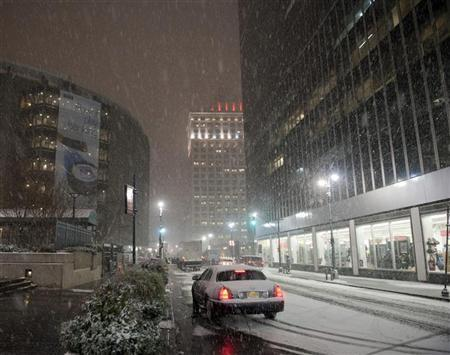 Snow falls outside Madison Square Garden (L) as a storm arrives in New York January 11, 2011. REUTERS/Ray Stubblebine (UNITED STATES - Tags: ENVIRONMENT IMAGES OF THE DAY)