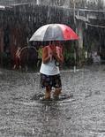 <p>Женщина идет по затопленной улице города Параньяк 25 июля 2010 года. Проливные дожди и наводнения в центре и на юге Филиппин унесли жизни 42 человек, а также нанесли ущерб посевам и инфраструктуре страны на сумму более 1 миллиарда песо ($23 миллиона), сообщило министерство по борьбе с последствиями стихийных бедствий. REUTERS/Romeo Ranoco</p>
