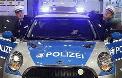 <p>Сотрудники полиции позируют фотографу у служебного автомобиля Mini на автошоу в Эссене 26 ноября 2010 года. Двое мужчин сообщили в немецкую полицию о совершенном ими правонарушении, попросив помочь выбраться из застрявшего лифта. REUTERS/Ina Fassbender</p>