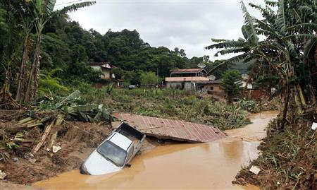 A partially submerged vehicle is seen after a landslide in Teresopolis January 13, 2011. REUTERS/Bruno Domingos