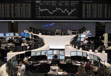 Traders are pictured at their desks in front of the DAX board at the Frankfurt stock exchange January 13, 2011. REUTERS/Remote/Amanda Andersen
