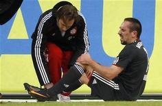 <p>Franck Ribery (dir) do Bayern de Munique é atendido por uma autoridade da equipe após sofrer uma entrada no jogo contra o VfL Wolfsburg. Ribery vai perder apenas cinco dias de treino após contundir seu joelho esquerdo no empate de 1 x 1 no sábado. 15/01/2011 REUTERS/Christian Charisius</p>