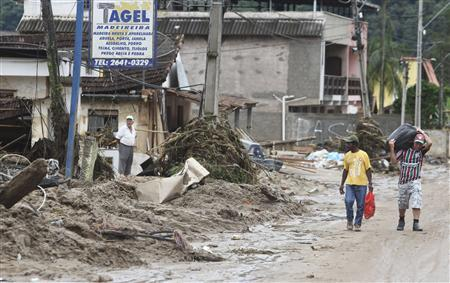 Men (R) carrying their belongings walk by houses damaged by a landslide in Vieira January 16, 2011. REUTERS/Bruno Domingos