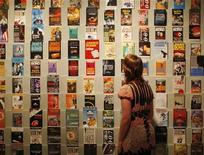 """<p>Девушка смотрит на коллекцию книг Яна Флеминга про Джеймса Бонда на выставке в Лондоне 16 апреля 2008 года. Новая книга о Джеймсе Бонде, написанная американским писателем Джеффри Дивером, получит название """"Карт-бланш"""" и отправит британского спецагента в Дубай. REUTERS/Stephen Hird</p>"""