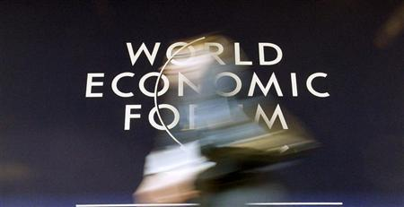 A woman walks past the logo of the World Economic Forum (WEF) at the congress centre of the Swiss mountain resort of Davos January 29, 2010. REUTERS/Arnd Wiegmann (POLITICS BUSINESS)