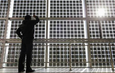 A visitor looks at the solar cells which are incorporated into window glasses in the Shanxi Nyke Solar Energy Technology company in Taiyuan, Shanxi province December 3, 2010. REUTERS/Stringer (CHINA - Tags: ENERGY