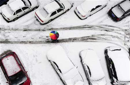 A man is seen beneath an umbrella as he walks past vehicles amid snowfall in Changsha, Hunan province January 19, 2011. REUTERS/China Daily (CHINA - Tags: ENVIRONMENT TRANSPORT IMAGES OF THE DAY) CHINA OUT.