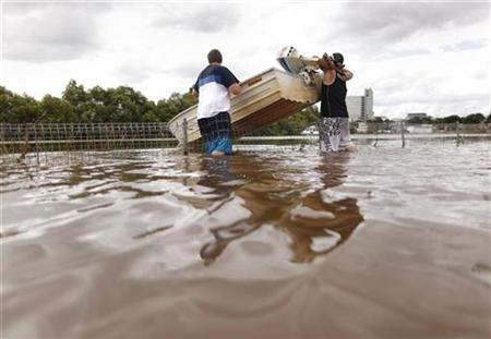 Two men lift their boat over a fence as they travel through flooded streets, in a commercial area of Brisbane January 13, 2011. REUTERS/Tim Wimborne