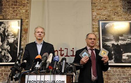 WikiLeaks founder Julian Assange (L) prepares to receive CD's containing data on offshore bank account holders from former Swiss private banker Rudolf Elmer at the Frontline club in London, January 17, 2011. REUTERS/Paul Hackett