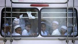 <p>Дети смотрят в окно автобуса, везущего их домой после школы, в Коломбо 4 октября 2009 года. Южноафриканская полиция арестовала в среду водителя, который перевозил 116 школьников в автобусе, рассчитанном на 62 пассажира, сообщила представитель полиции. REUTERS/Carlos Barria</p>