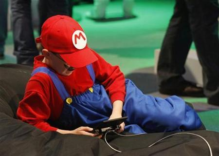 A boy dressed as ''Mario'' plays with a Nintendo DS at an exhibition stand during the Gamescom 2010 fair in Cologne August 19, 2010. REUTERS/Ina Fassbender