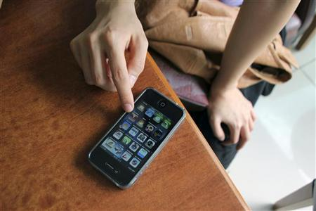 Traveller Sul-hee Kim, 25, of Seoul, looks for travel applications on her iPhone 4G at a restaurant in the Sultanhamet area of Istanbul, Turkey, in this September 30, 2010 file photo. REUTERS/Natalie Armstrong