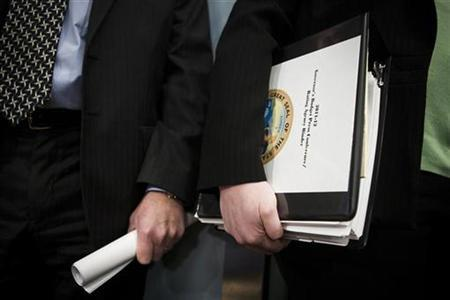 California Governor Jerry Brown's Finance Director Ana Matosantos (R) holds his budget proposal in Sacramento, California January 10, 2011. REUTERS/Max Whittaker