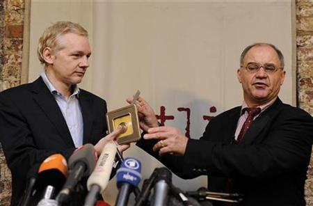 WikiLeaks founder Julian Assange (L) receives CD's containing data on offshore bank account holders from former Swiss private banker Rudolf Elmer at the Frontline club in London, January 17, 2011. REUTERS/Paul Hackett
