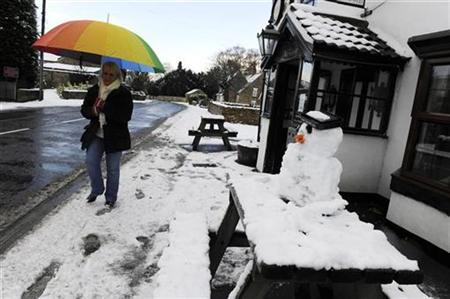 A woman walks past a snowman in the street at Sutton-In-Whitestonecliffe, northern England, November 25,2010. REUTERS/Nigel Roddis