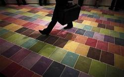 <p>A man walks over a colourful carpet in this file photo. REUTERS/Johannes Eisele</p>