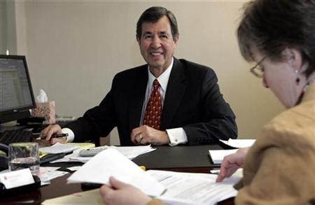 Pointe Capital Management LLC managing member Chuck Huebner (L) takes part in a conference call with his Director of Administration Susan Doughty in his new office at Grosse Pointe Farms, Michigan March 23, 2010. REUTERS/Rebecca Cook