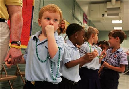 Pre-schooler Cecil Smith (L), 4, holds the hand of a teacher's assistant as he prepares to go to class after he and classmates were given Mardi Gras beads, on the first day of school since Hurricane Katrina hit over a month ago, at an elementary school in Metairie, Louisiana October 3, 2005. REUTERS/Lee Celano