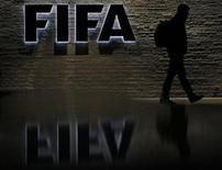<p>Мужчина проходит мимо логотипа ФИФА у входа в штаб-квартиру организации в Цюрихе 20 октября 2010 года. Чемпионат мира 2022 года в Катаре может пройти в конце года, сказал президент ФИФА Зепп Блаттер во вторник. REUTERS/Christian Hartmann</p>