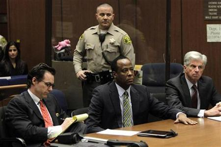 Doctor Conrad Murray (C), the late Michael Jackson's personal physician, sits with his lawyers Edward Chernoff (L) and Michael Flanagan during his arraignment on a charge of involuntary manslaughter in the pop star's death, in Los Angeles, California, January 25, 2011. REUTERS/Irfan Khan/Pool