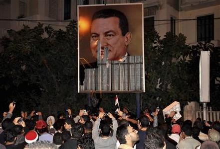 Anti-government protesters stand next to a defaced picture of Egypt's President Hosni Mubarak in Alexandria, 230 km (140 miles) north of Cairo, January 25, 2011. REUTERS/Stringer
