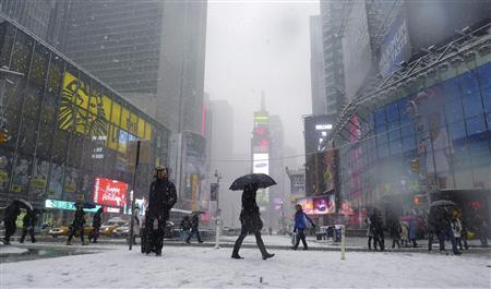 People walk through Times Square as snow falls in New York, January 26, 2011. REUTERS/Gary Hershorn