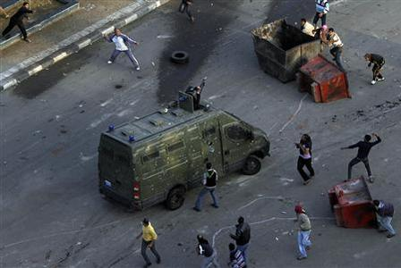 Egyptian anti-government protesters attack a riot police car at the port city in Suez, about 134 km (83 miles) east of Cairo east of Cairo, January 27, 2011. REUTERS/Mohamed Abd El-Ghany