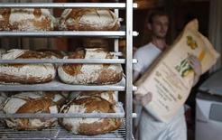 <p>A French baker carries a bag of flour near freshly-baked traditional bread in Strasbourg eastern France August 6, 2010. REUTERS/Vincent Kessler</p>