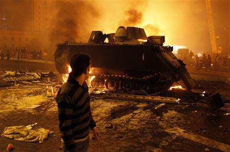 A protester looks at a burnt Egyptian Army armoured vehicle in downtown Cairo, January 28, 2011. REUTERS/Goran Tomasevic