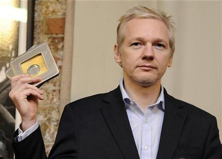 WikiLeaks founder Julian Assange holds up CD's containing data on offshore bank account holders, which he received from former Swiss private banker Rudolf Elmer at the Frontline club in London, January 17, 2011. REUTERS/Paul Hackett