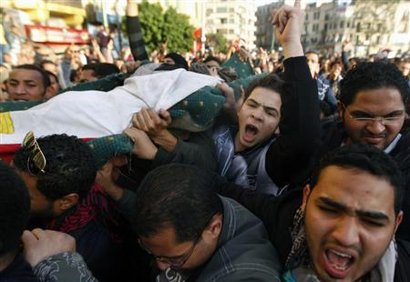 Protesters carry the body of a man killed during an attempt to storm the interior ministry in Cairo January 29, 2011. REUTERS/Yannis Behrakis
