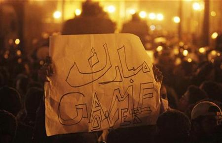 A protester holds a banner reading ''Mubarak: game over'' as they demonstrate at midnight in downtown Cairo January 26, 2011. REUTERS/Asmaa Waguih