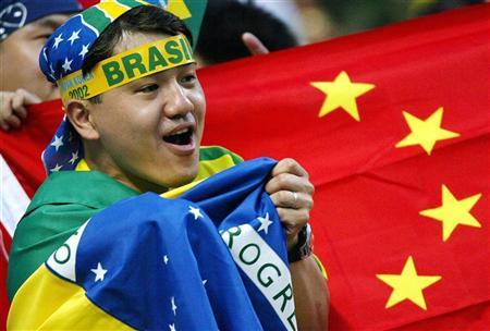 A supporter of Brazil cheers in front of China's flag before the begining of a Group C match between Brazil and China at the World Cup Finals in Sogwipo, June 8, 2002. REUTERS/Jerry Lampen