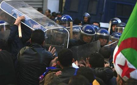 Protesters are pushed back by riot police during a demonstration in downtown Algiers, January 22, 2011. REUTERS/Farouk Batiche