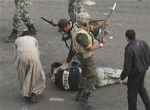 <p>A member of the press lies on the ground after being attacked by mobs while soldiers surround him in Cairo, February 3, 2011. REUTERS/Kyodo</p>