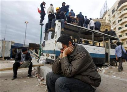 An injured anti-government protester rests by a burned out bus, used as barricade, alongside the Egyptian Museum near Tahrir Square in Cairo February 4, 2011. REUTERS/Yannis Behrakis