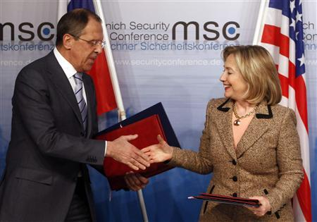 U.S. Secretary of State Hillary Clinton and Russian Foreign Minister Sergei Lavrov exchange documents formally bringing into force the landmark nuclear arms reduction pact START during the 47th Conference on Security Policy in Munich February 5, 2011. REUTERS/Michael Dalder