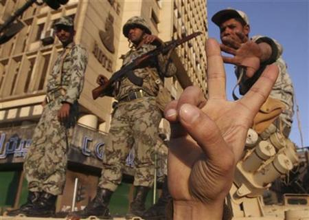 A protester gestures in front of Egyptian soldiers as they block a street during an anti-government protest in Tahrir square in Cairo January 31, 2011.REUTERS/Suhaib Salem