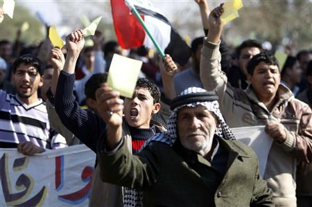 Residents carry yellow cards as they protest to demand for better basic services and the release of detainees in Basra, 420 km (260 miles) southeast of Baghdad February 6, 2011. REUTERS/Atef Hassan