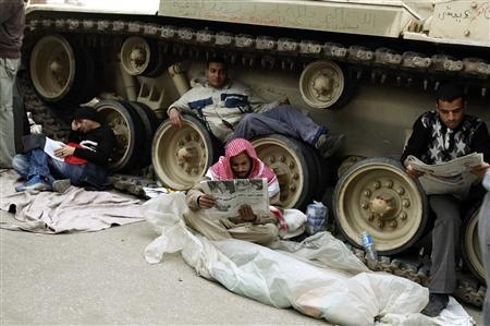 Anti-government supporters rest by an Egyptian army tank in Tahrir Square in Cairo February 6, 2011. REUTERS/Dylan Martinez