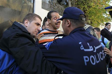 Policemen try to calm down a man (C) who tried to set himself on fire during a small protest held by unemployed people outside the employment ministry building in Algiers February 6, 2011. REUTERS/Zohra Bensemra