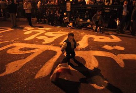 A child walks with an Egyptian flag in the middle of freshly written anti-Mubarak slogans, with the word 'unfair' visible, at Tahrir Square in Cario February 6, 2011. REUTERS/Asmaa Waguih