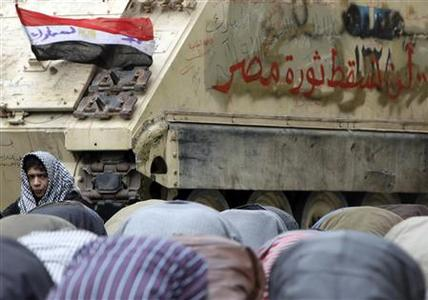 An Egyptian anti-government protestor reacts as others pray around army vehicles at Tahrir Square in Cairo February 7, 2011. REUTERS/Amr Abdallah Dalsh