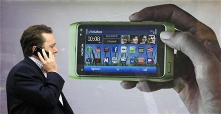 A man talks on his mobile phone as he walks past an advertisment for the new Nokia N8 on Oxford Street in London, September 30, 2010. EUTERS/Luke MacGregor