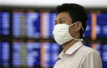 A traveller wears a mask as he waits at the airport in Hong Kong June 12, 2009, a day after the World Health Organization (WHO) declared an influenza pandemic and advised governments to prepare for a long-term battle against an unstoppable Influenza A (H1N1) flu virus. REUTERS/Aaron Tam