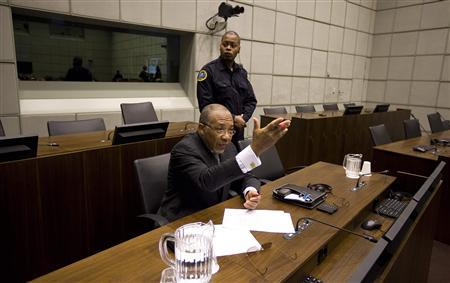 Former Liberian President Charles Taylor (bottom) awaits the start of the prosecution's closing arguments during his trial at the U.N.-backed Special Court for Sierra Leone in Leidschendam February 8, 2011. The defence lawyer for Taylor walked out of the Sierra Leone war crimes court on Tuesday in protest at a decision by judges preventing him from filing a final summary of his evidence. Taylor denies all 11 charges of instigating murder, rape, mutilation, sexual slavery and conscription of child soldiers during wars in Liberia and Sierra Leone in which more than 250,000 were killed. REUTERS/Jerry Lampen