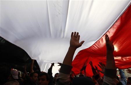 Opposition supporters carry a huge Egyptian flag amid the crowd in Tahrir Square in Cairo February 9, 2011. REUTERS/Yannis Behrakis