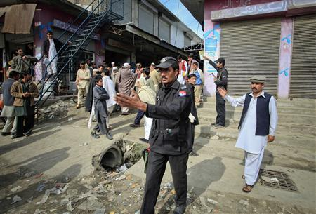 Policemen ask residents to disperse as they stand near the site of a suicide bomb attack at a paramilitary training centre in Mardan, northwest Pakistan February 10, 2011. REUTERS/Fayaz Aziz