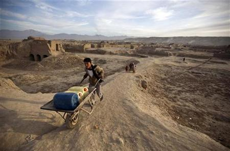 An Afghan man pushes a hand cart with water containers near a public water pump in Kabul January 13, 2010. REUTERS/Ahmad Masood